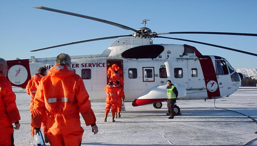 Idemitsu staff walking towards a helicopter offshore. Photo: IPN